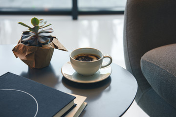Close-up view of green succulent, cup of coffee and books on table indoors