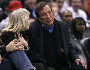 File photo of Clippers owner Sterling with a companion as he watches team play Knicks in NBA game in Los Angeles