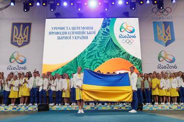 Ukrainian Olympic team members rhythmic gymnast Rizatdinova and diver Kvasha hold national flag during an official farewell ceremony for the 2016 Rio Olympic Games in Kiev