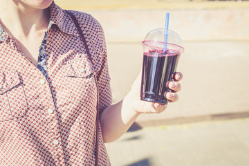 Woman holding berry drink in plastic cup with straw