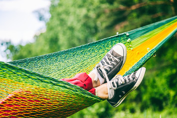 Female legs in sneakers in a hammock, summer concept, outdoor recreation, vacation