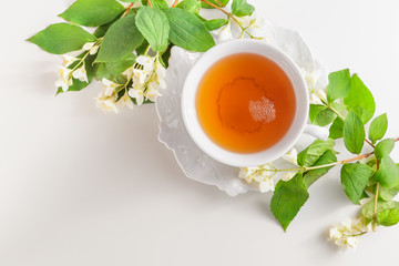 Cup of tea with jasmine flowers on a white table