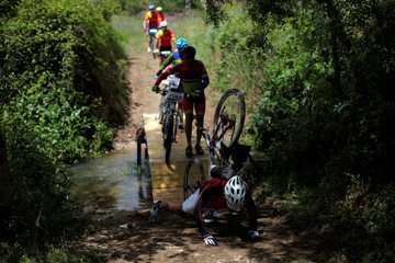 A mountain biker falls as he crosses a river while participating in the cycling category in the XIX 101km international competition in Ronda