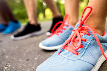 Legs of young athletes prepared for run in green sunny park.