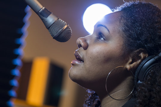 Black female singing in a recording studio, close up