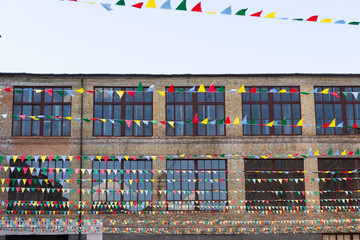 Big windows of old building beside hanging multi-colored flags