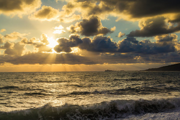 Beautiful sunset among the unimaginable clouds with glimpses of rays on the sea with waves