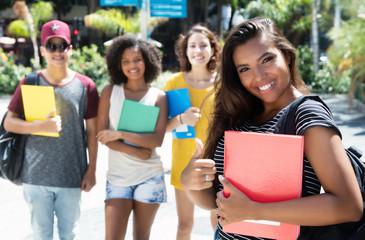 Südamerikanische Studentin zeigt den Daumen mit anderen Studenten