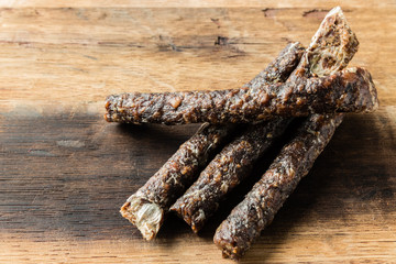 A Caucasian hand holding a stick of droewors (dried meat), this is a traditional food snack found in South Africa.