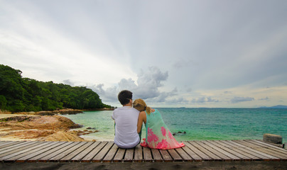 Men and women sitting together on wooden walkway looking sea and sky