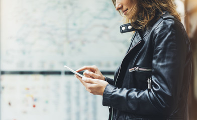 Fotomurales - Girl in leather jacket holding smart phone on background map light box in city, hipster using in female hands and texting mobile, street lifestyle, tourist planing route in summer concept