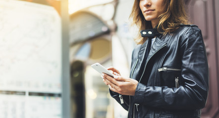 Fotomurales - Girl in leather jacket holding smart phone on background map light box in sun city, hipster using in female hands and texting mobile, street lifestyle, tourist planing route in summer concept