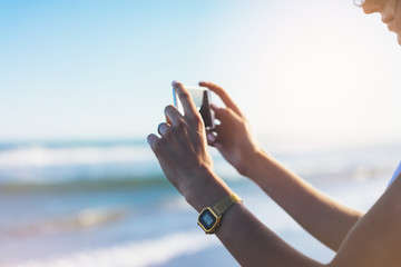 Hipster girl photograph on smart phone gadget in sand coastline, mock up of blank screen. Traveler hold and using in female hand mobile on background seascape horizon on blue sun ocean, lifestyle