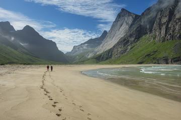 Two hikers leave footprints in sand at Horseid beach