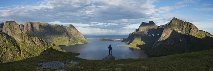 Female hiker takes in panoramic view over Reinefjord and surrounding mountains