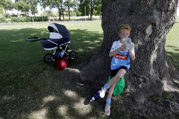 A boy rests in the shadow of an oak in the middle of  soccer pitch in Orissaare