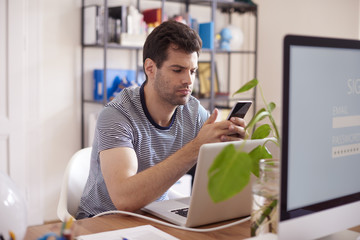 Young businessman using smartphone at office