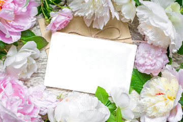 blank greeting card and envelope in frame of pink and white peonies and roses