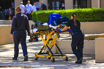 Paramedics pushing a gurny loaded with life saving equipment in Santa Barbara CA, USA