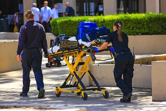 Paramedics pushing a gurny loaded with life saving equipment in Santa Barbara CA, USA