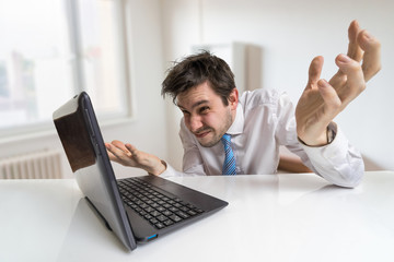 Young confused man is working with laptop.