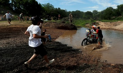 People run to help KTM motorcycle rider Sanz of Spain during the Buenos Aires-Rosario prologue stage of Dakar Rally 2016 in Arrecifes