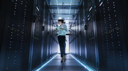 Female IT Engineer Walking through Data Center Corridor. She is Holding Tablet Computer. She is Blurred in Motion.
