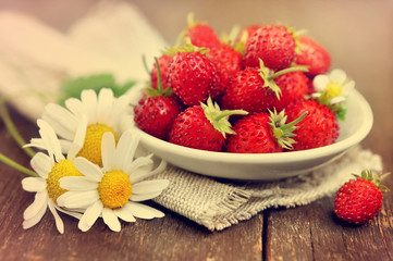 Sweet wild strawberries in plate with chamomiles on wooden background, toned