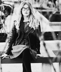 blonde gir sits on a bench, summer city, black and white picture