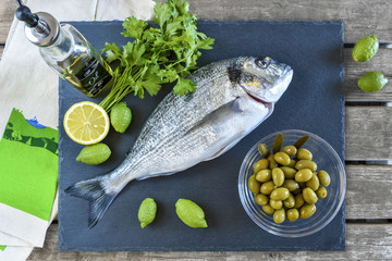 One ready to cook raw bream fish with lemon and olives on stone slate board.