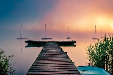 Morning foggy lake landscape. Wooden pier and boats on the lake.