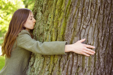 Young woman hugging and kissing tree