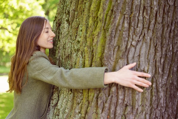 Smiling brunette woman hugging tree trunk