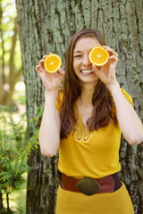 Cute vivacious young woman with sliced orange