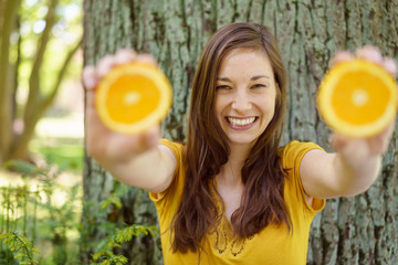 Happy young woman holding fresh oranges