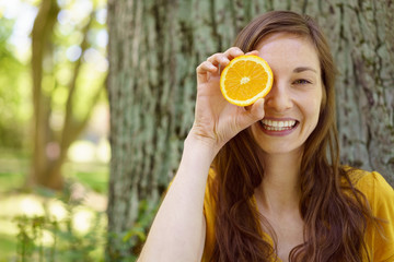 Playful young woman holding an orange to her eye