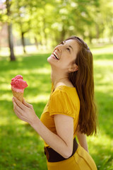 Happy woman with ice cream in park