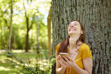 Happy young woman listening to music on a mobile