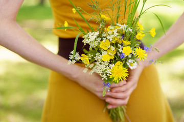 Woman hiding a posy of flowers behind her back