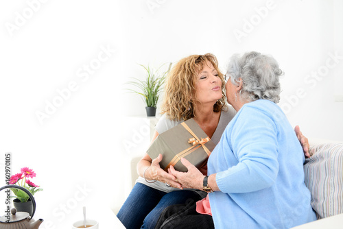 mature woman offering present gift to elderly senior lady for mother's day or birthday anniversary