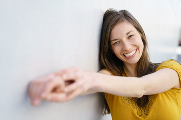 Cheerful young woman holding out hands to camera