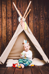 Child, boy, playing in tent indoors on a wooden background. Dressed in Indian