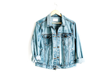 Beautiful trendy blue denim jeans jacket on hanger near white background. Fashion concept. Flat lay, top view