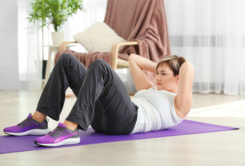 Mature woman doing sit-ups at home. Weight loss concept