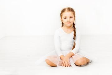 Little dancer sitting on floor of ballet studio