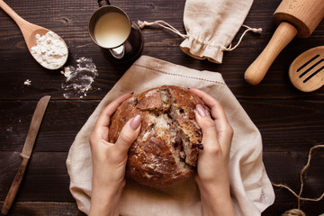 Hands holding fresh homemade bread on the dark wooden background top view