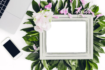 wooden frame decorated with flowers and leaves, laptop and phone. empty space for text
