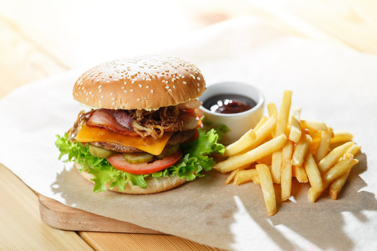 Big tasty burger and fries on the wooden table