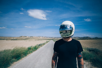 Front shot of attractive brutal unrecognizable man in black tshirt and blue denim jeans, wears vintage helmet in middle of american highway road