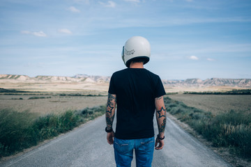 Photo from the back of brutal masculine man with authentic arm tattoos in blank black mockup tshirt standing in middle of desert highway